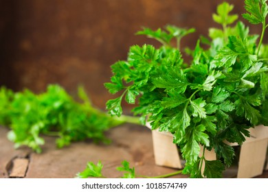 Parsley leaves in a bowl on a wooden table.