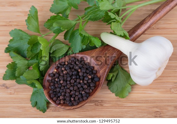 parsley,  peppers and garlic on a wooden background