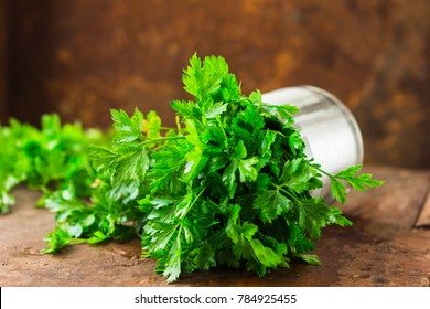 Parsley sprigs in a silver metal bowl on wooden board.  Organic effective source of anti-oxidant nutrients, vitamin K, vitamin C and vitamin A.