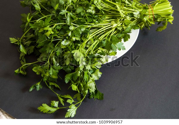 the parsley stands in the plate, the parsley plant on the black floor,