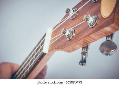 Part of an acoustic guitar on a grey background