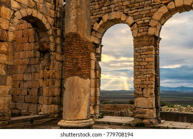 Part of the ancient Roman ruins in Volubilis Morocco with a spectacular light show, just before sundown.