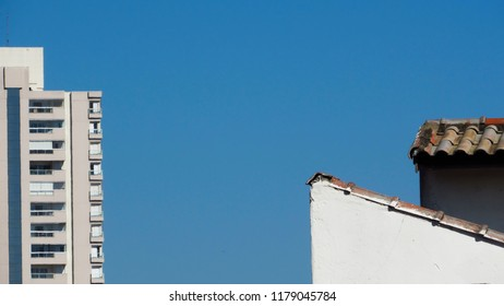 part of an apartment building and a storey occupying the ends of the photo separated by a very limpid blue sky, sao paulo, brazil
