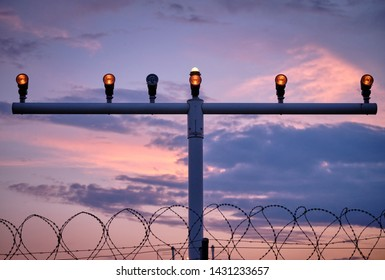 A part of the approach lighting system of an airport to help pilots while landing in front of sunset sky