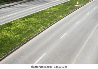 Part of asphalt motor road with dividing strip of green grass