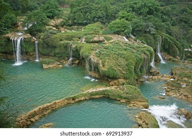 A part of Ban Gioc waterfall in Vietnam with huge amount of water and misty scene on the river below.