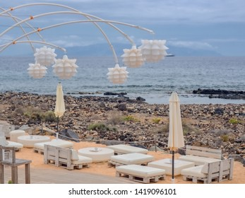 Part of a beach bar directly on the wild beach on the Atlantic Ocean on the Canary Island of Tenerife, white imitation leather furniture and a modern white lamp lighting above,quiet ambience,