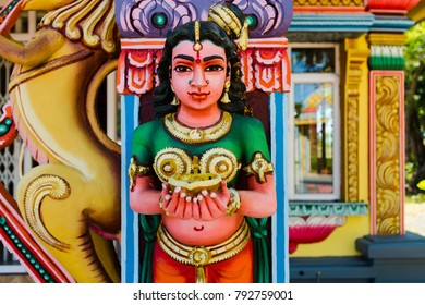 Part of a beautiful and colorful Indian temple in Mauritius Island. Close-up on sculptures and statues of Indian deities.