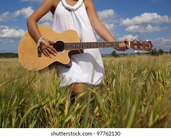 Part of beautiful girl playing guitar in field over blue sky. Freedom
