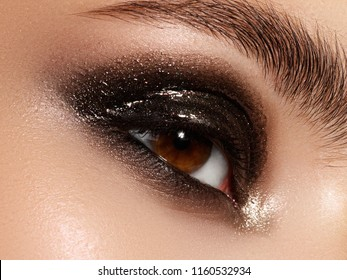 Part of beauty face. Close up of blue woman eye with beautiful brown with shades smokey eyes makeup. Modern fashion make up. Nude makeup. Clean skin, Long lashes