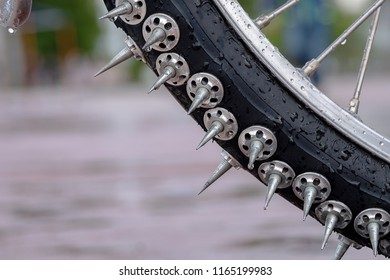 part of the Bicycle wheel covered with large metal spikes in the background of asphalt