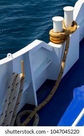 Part of the blue white ferry - ship on the sea, metal bollard with mooring rope; travel, vacation, transport, background.