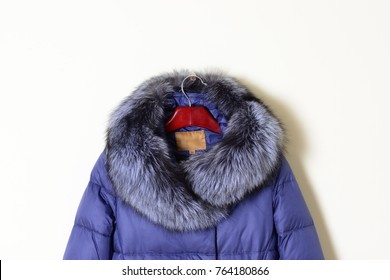 Part of blue woman's jacket, down jacket with a hood with natural fur. Outerwear. Stylish women's jacket, isolated on white background. Close up.