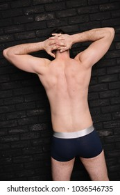 part of body: back is broad and inflated male buttocks. clean skin and short hair. stretching after workout and athletic figure after diet. beach style in clothes: boxer briefs
