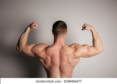 part of body: back is broad and voluminous inflated shoulders. anatomy of the male body. male bodybuilder posing on the old background and shows a relief of muscles