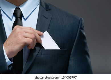 Part of body of business man who takes out business card from the pocket of business suit, copyspace