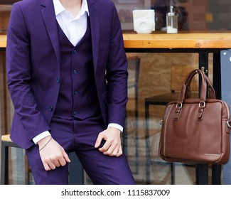 Part of the body. Fashion man. A young hipster businessman with a beard in a trendy purple suit with a trendy handmade leather bag.