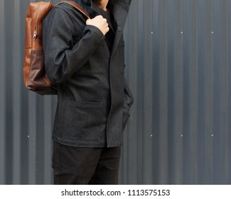 Part of the body. Tourism and Fashion. A city portrait of a young bearded hipster tourist in a fashionable dark blue jacket and with a trendy brown backpack against the backgrou