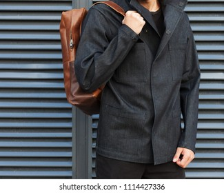 Part of the body. Tourism and Fashion. Urban portrait of a young bearded hipster tourist in a fashionable dark blue jacket and with a trendy brown backpack against a wall of gray metal. Outdoor.