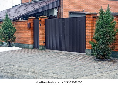 Part of a brick fence with closed gates and decorative pine trees on the street