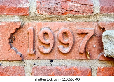 Part of a brick wall with an embossed 1997 sign