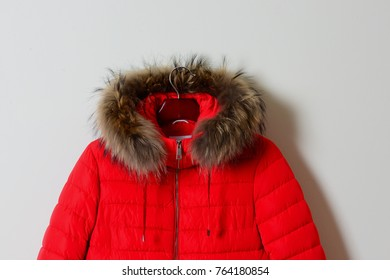 Part of a bright red female jacket with a hood on a natural raccoon fur, with a zipper. Outerwear. Stylish women's jacket, isolated on a beige background. Close-up.