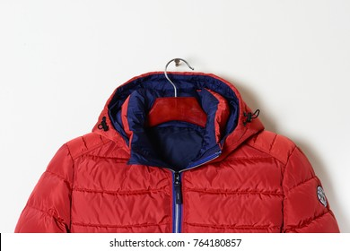 Part of a bright red jacket is a down jacket with a hood and an unbuttoned collar. Winter outerwear for men. Close-up.