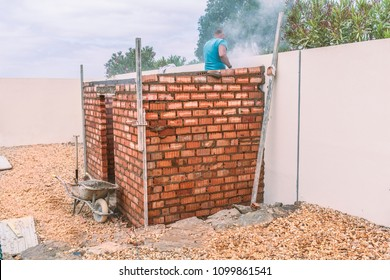 Part build construction of a brick shed. A  bricklayer can be seen working creating dust. the construction is a small brick shed or out house