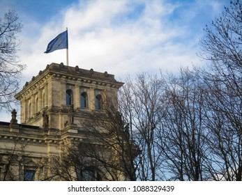 Part of Bundestag, seat of Grman government, with european flag over blue sky
