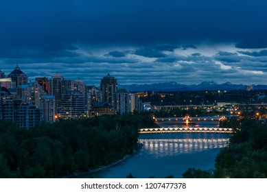 Part of the Calgary skyline with the Bow river and the Peace Bridge, designed by Santiago Calatrava, just before dark. You can clearly see the Rocky Mountains in the background.