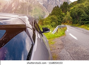 Part of the car close-up on the road in mountains on summer day