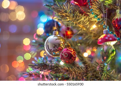 Part of Christmas tree, with colorful glass balls, small decorations and colorful light reflections