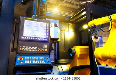 part of the cnc milling machine with control panel and robot in motion blur moves a part from the CNC on the conveyor