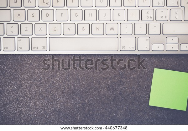 part of computer keyboard and blank paper on a stone surface - copy space