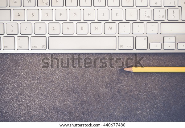 part of computer keyboard and pencil  on a stone surface - copy space