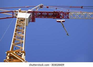 Part of a construction tower crane against the blue sky, copy space