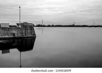 Part of a dam wall with a lantern reflected in the water on a calm lake under cloudy sky