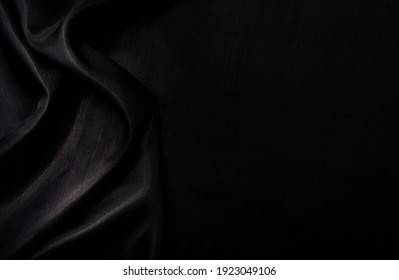 Part of the dark fabric texture of the fabric for the background and decoration of the work of art, a beautiful crumpled pattern of silk or linen. A crumpled piece of cloth