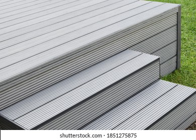 Part of dark gray or anthracite wpc composite material terrace deck with stairs  in backyard green grass outdoors.