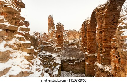 part of the destroyed old fortification made of red brick from clay, winter and snow
