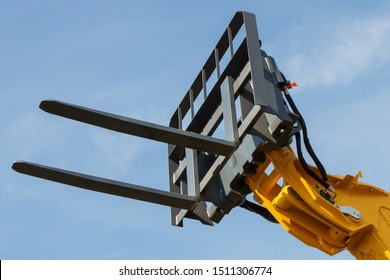 Part and detail of forklift loader or stacker on blue sky background. Modern technology