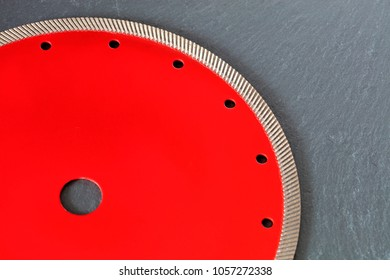 Part of a diamond red disc for cutting against a gray granite background close-up.