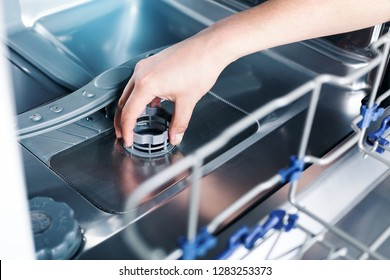 Part of dishwasher filter in male hand, cleaning service of home appliance dish washing machine inside,