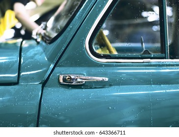 Part of the door of an antique car with an opening handle with a shallow depth of field