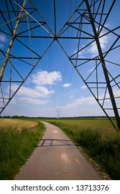 a part of electric tower in a nice landscape with farmland and blue sky