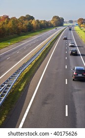 Part of a european highway with cars in motion.
