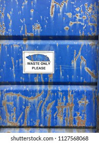Part of the exterior of a rusty blue waste bin