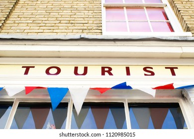 Part of the exterior of a tourist office in the UK with colourful bunting
