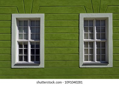 Part of facade of old building with two windows on green wall is located on one of streets of Kamianets-Podilskyi, Khmelnytskyi region, Ukraine