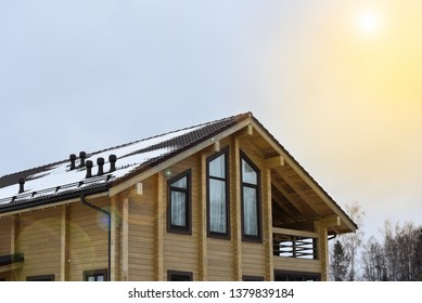 Part of the facade of a wooden house in modern style and sun rays. Natural photo.